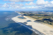 Nederland, Zuid-Holland, Gemeente Westland, 28-04-2017; Delflandse Kust ter hoogte van Ter Heijde en Monster, Den Haag aan de horizon. De Zandmotor is een kunstmatig schiereiland / landtong, ontstaan door het opspuiten van zand voor de kust. Wind, golven en stroming zullen het zand langs de kust in noordelijke richting verspreiden waardoor verderop langs de kust bredere stranden en duinen ontstaan. De zandmotor is een experiment in het kader van kustonderhoud en kustverdediging. <br /> Sand Engine, artificial peninsula build by the raising of sand for the coast of Ter Heijde (near the Hague, at the horizon). Wind, waves and currents will distribute the sand along the coast yielding wider beaches and dunes along the coastline. The Sand Engine is a experiment for coastal maintenance of coastal defense.<br /> luchtfoto (toeslag op standard tarieven);<br /> aerial photo (additional fee required);<br /> copyright foto/photo Siebe Swart
