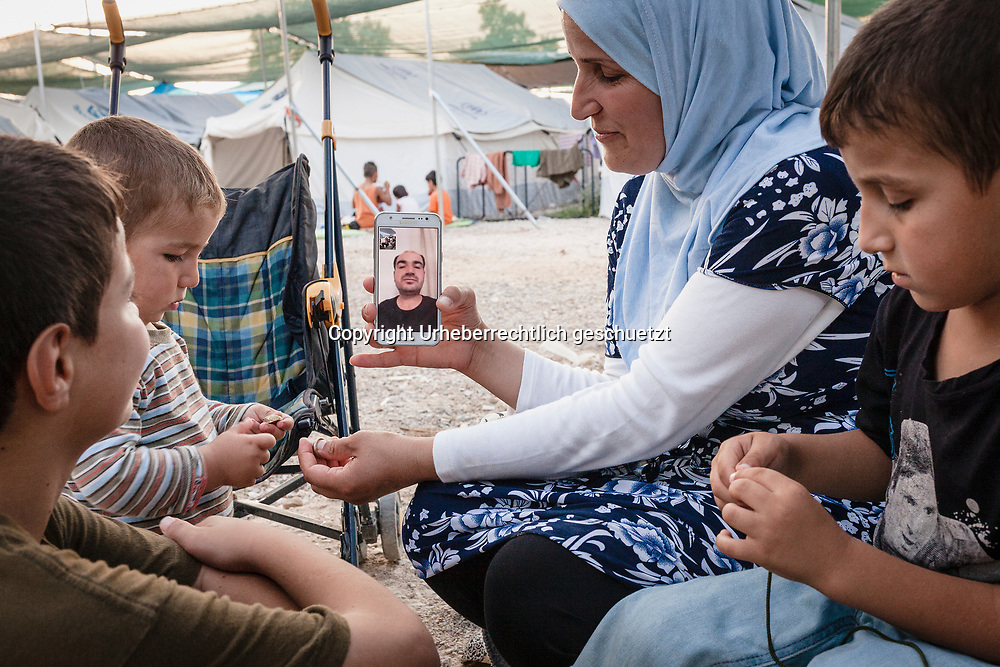 Greece, Lagkadikia, Refugee Camp, Hayfa (C), age 34,  and her sons talking via skype with Mazkin, husband and father, who lives in Berlin. Sitting  outside their tent. Hayfa Sadiq, age 34, stays with her five boys age between 1,5 and 15 in this Refugee Camp since April 2016 waiting to get a Visa and acceptance from the German authorithies. Mohamad, age 12, (R 1) , Abdul Rahman, age 6, (L 1)  Abdulla, age 1,5 (R 2) Her husband, Mazkin, age 42, and father of the kids, is living in Berlin, Germany. He is accepted as refugee seeking asylum. They family is form Haseki, North Syria.