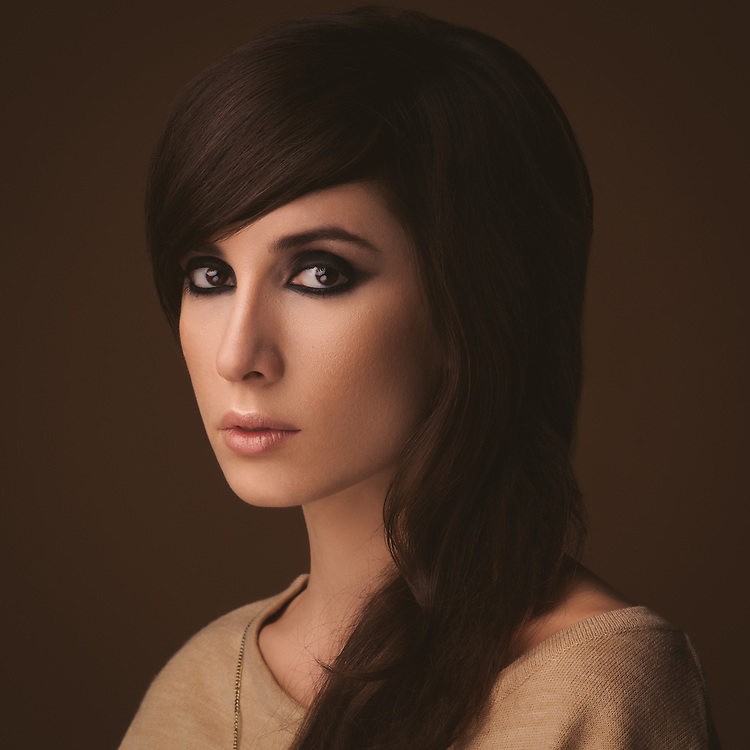 Studio portrait of a beautiful Caucasian woman against a brown background.
