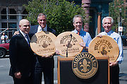 Michter's Distillery President Joseph J. Magliocco with Joe Reagan, president and CEO of Greater Louisville Inc., Louisville Mayor Greg Fischer and Kentucky Governor Steve Beshear hold engraved whiskey barrel tops after a news conference Wednesday, July 6, 2011 to announce plans to open a distillery in the historic Fort Nelson Building in downtown Louisville, Ky., across from the Louisville Slugger Museum and Factory by spring 2013. (Michter's photo by Brian Bohannon)