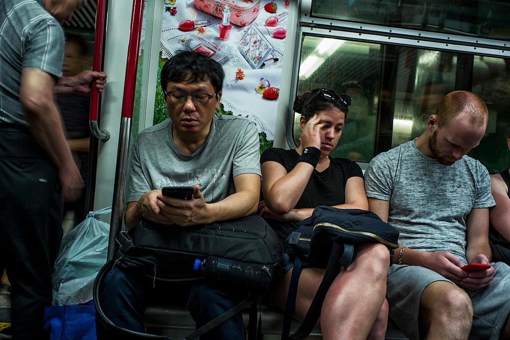 Hong Kong | 06.05.2017: Hong Kong <br /> <br /> hier: U-Bahn Passagiere mit Smartphones<br />  <br /> Sascha Rheker<br /> 20170506<br /> <br /> [Inhaltsveraendernde Manipulation des Fotos nur nach ausdruecklicher Genehmigung des Fotografen. Vereinbarungen ueber Abtretung von Persoenlichkeitsrechten/Model Release der abgebildeten Person/Personen liegt/liegen nicht vor.]