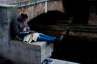 Man sitting next to a bridge over the River Seine, Paris