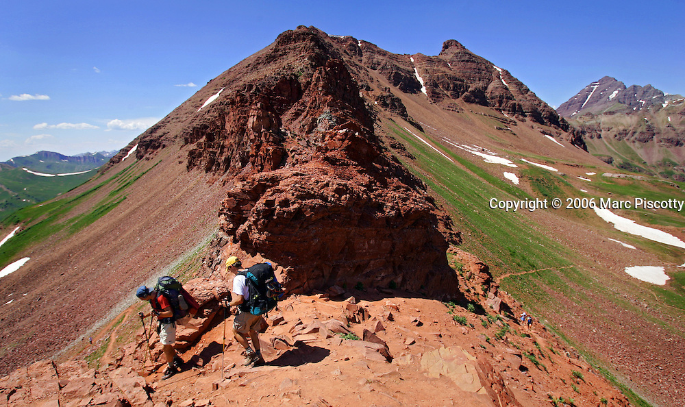 Aspen and Crested Butte are hours apart by car and probably worlds apart in attitude but only separated by 24 miles on a map. Many hikers are starting to take one of a number of mountain passes on foot and stay the night in the other town and then hike, bike, drive or fly back the following day. Depending on the route chosen and the ability of the hiker, it takes about 5 to 9 hours to hike between the two towns. Most hikers choose the trails that converge on 12,490-foot West Maroon Pass ? the shortest of the available options at 10.5 miles. The trail offers a steady uphill from either side, with ample time to prepare for the last steep and loose rocky sections before the pass. Backpackers Jeff Kennedy (left in red shirt) of Green Bay, Wis. and Michael Schultz (right in white shirt) of La Crosse, Wis. make the descent off of West Maroon Pass on to the Crested Butte side on the left after climbing to it from the Aspen side on the right. The two were making the Four Passes Loop and camping out in the area..(MARC PISCOTTY/ © 2006)