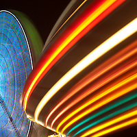 USA, New Jersey, Seaside Park, Light trails from ferris wheel and rides Boardwalk amusement park lights at night at Funtown Pier