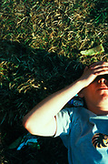 Man lying down on grass clasping head in sunshine, festival, U.K, 2000s.