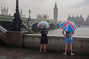 Wet tourists stand overlooking the River Thames from London's Southbank, enduring heavy summer rainfall in the capital.