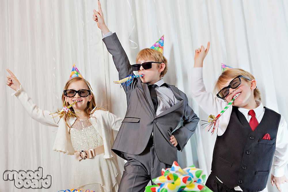 Brothers and sister wearing sunglasses and party puffer in mouth dancing