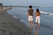 A couple takes an evening stroll on a beach in Narragansett, Rhode Island.