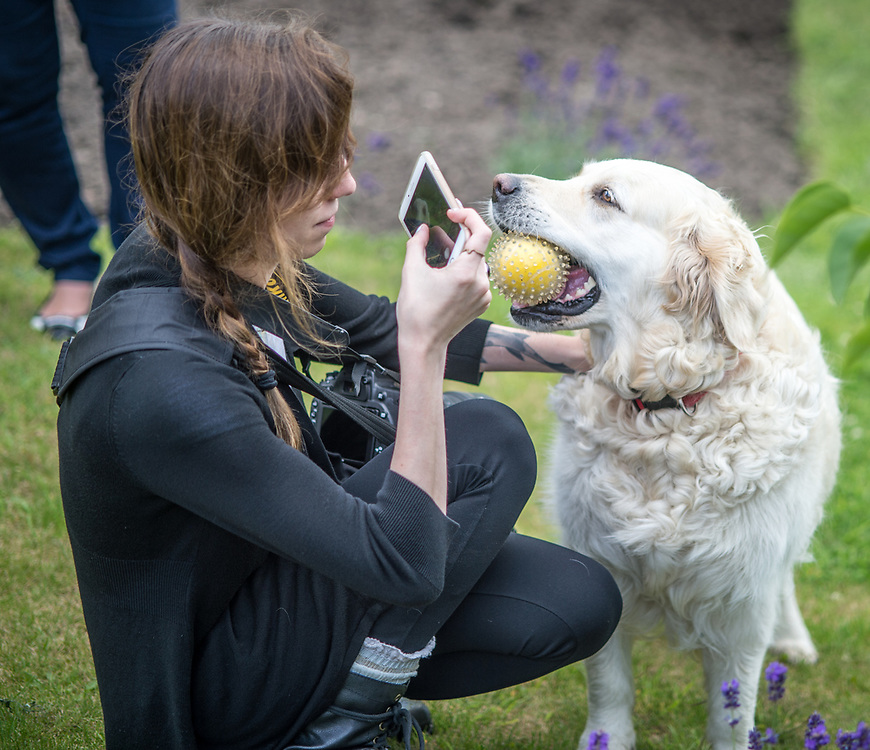 Young female takes photo of dog on smart phone, Richmond, Yorkshire, England