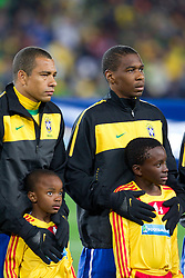 Gilberto Silva and Juan of Brazil warming up young boys during listening to the national anthem at the 2010 FIFA World Cup South Africa Group G match between Brazil and North Korea at Ellis Park Stadium on June 15, 2010 in Johannesburg, South Africa. Brazil defeated Korea 2-1. (Photo by Vid Ponikvar / Sportida)