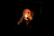 Roscigno Vecchia, Italia - 27 maggio 2012. Giuseppe Spagnuolo, unico abitante del piccolo paese di Roscigno Vecchia ritratto all'interno della sua bitazione mentre accende la sua pipa. Il paese ha incominciato a svuotarsi nel 1902 a causa delle frequenti frane per poi diventare totalmente disabitato nel 2000. Ogni tanto arrivano a Roscigno Vecchia dei turisti a cui Giuseppe Spagnuolo fa da cicerone..Ph. Roberto Salomone Ag. Controluce.ITALY - Giuseppe Spagnuolo, the only inhabitant of the small ghost town of Roscigno Vecchia, portrayed in his house. The town counts only Mr. Spagnuolo as inhabitant since 2000. Now and then few tourists show up and Giuseppe Spagnuolo gives them the tour of the town.
