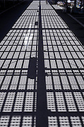 shadow of overhead metal grating projected on empty road