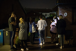 © Licensed to London News Pictures . 25/07/2017 . Oldham , UK . People look on as a window is lit up from outside by what is believed to be a police searchlight , at the scene where an armed siege that began at 3.15am on Tuesday 25th July in a house on Pemberton Way in Shaw , is ongoing in to a second night . A man named locally as Marc Schofield is reported to be holding a woman hostage after earlier releasing two children . The gas supply in the area has been cut off and several neighbouring properties have been evacuated . Photo credit : Joel Goodman/LNP