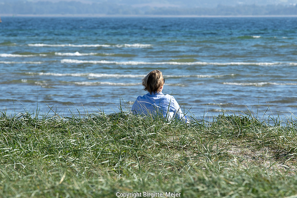 Female sitting by the beach on a late summers Day in Denmark Scandinavia, looking towards the sea.