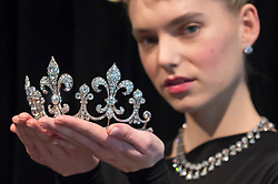 "© Licensed to London News Pictures. 19/10/2018. LONDON, UK. A model presents a diamond tiara, Hübner, circa 1912, of a fleur de lys design, with diamonds (USD350k-550k) and wears a diamond parure (USD300k-500k), both from Charles X, King of France. Preview of Sotheby's ""Royal Jewels from the Bourbon-Parma Family"", a family descended from Louis XIV of France, the Holy Roman Emperors and from Pope Paul III, with links to the most important ruling families of Europe.  Led by a breath-taking group of jewels which once belonged to Marie Antoinette, queen of France, the collection of jewels will be offered for sale at Sotheby's in Geneva on 14 November 2018.  Photo credit: Stephen Chung/LNP"