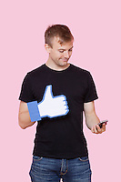 Young man with cell phone holding fake like button against pink background