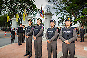 "24 JUNE 2014 - BANGKOK, THAILAND: Thai police officers line the sidewalk while members of the ""Monsoon Poets Society"" gather in front of the Anantasamakom Throne Hall Tuesday to pay homage to the People's Party, a Siamese (Thai) group of military and civil officers (which became a political party) that staged a bloodless coup against King Prajadhipok (Rama VII) and changed Thailand (then Siam) from an absolute monarchy to a constitutional monarchy on 24 June 1932. Since the coup against the civilian government on 22 May, the ruling junta has not allowed political gatherings. Although police read the poems, they did not arrest any of the poets or make any effort to break up the gathering.     PHOTO BY JACK KURTZ"