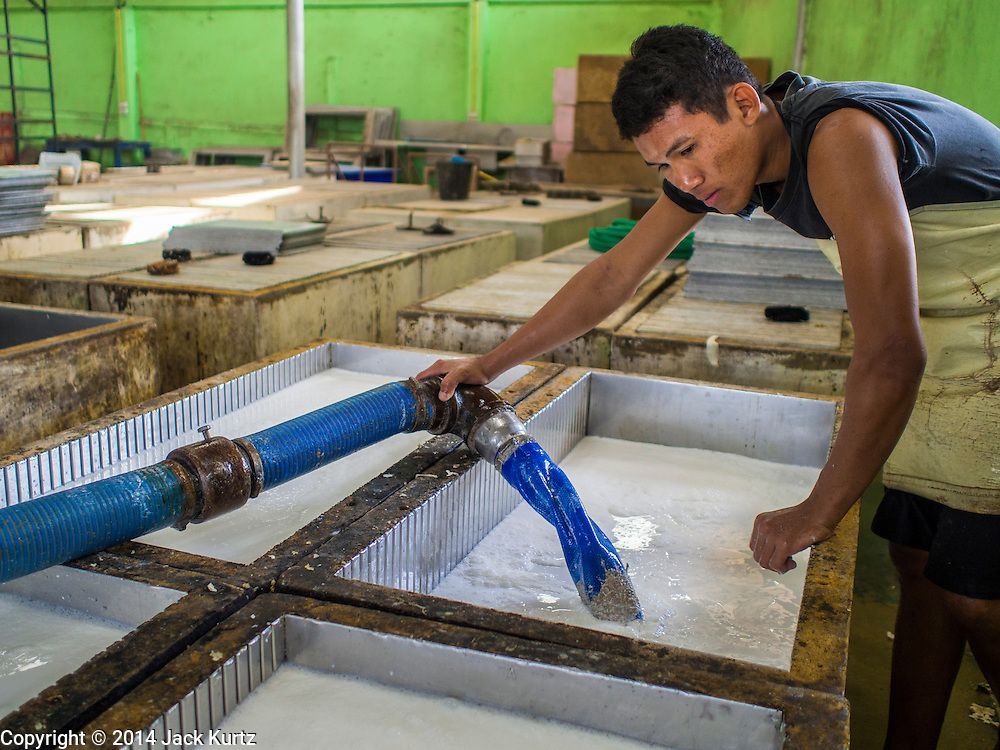 """16 DECEMBER 2014 - CHUM SAENG, RAYONG, THAILAND: A worker fills tanks with liquid latex to make rubber sheets on large rubber plantation near Chum Saeng, Thailand. The latex will be made into smoked rubber sheets. Thailand is the second leading rubber exporter in the world. In the last two years, the price paid to rubber farmers has plunged from approximately 190 Baht per kilo (about $6.10 US) to 45 Baht per kilo (about $1.20 US). It costs about 65 Baht per kilo to produce rubber ($2.05 US). Prices have plunged 5 percent since September, when rubber was about 52Baht per kilo. Some rubber farmers have taken jobs in the construction trade or in Bangkok to provide for their families during the slump. The Thai government recently announced a """"Rubber Fund"""" to assist small farm owners but said prices won't rebound until production is cut and world demand for rubber picks up.    PHOTO BY JACK KURTZ"""