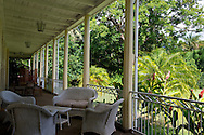 Wicker chairs on the porch overlooking the tropical garden at Eureka House, a preserved colonial style house built in 1830.  Moka, Mauritius, The Indian Ocean