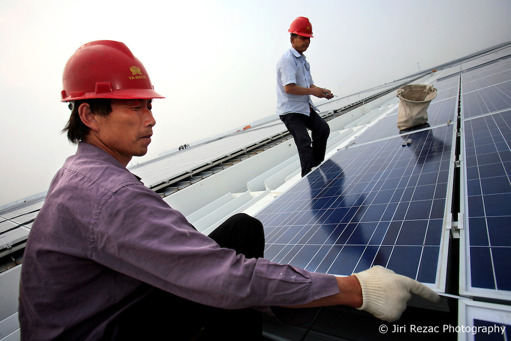 CHINA SHANGHAI HONGQIAO 19MAY10 - Workers install solar photovoltaic panels on the roofs of the Hongqiao Passenger Rail Terminal in Shanghai, China. There are a total of 23000 solar panels planned for the CECIC-funded project, each panel with a production capacity of 280 KWh to feed into the electricity grid.<br /> <br /> jre/Photo by Jiri Rezac / The Climate Group<br /> <br /> © Jiri Rezac 2010