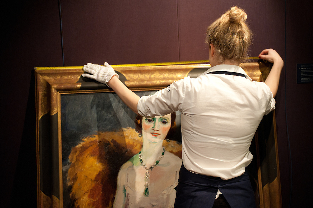 A Sotheby's employee works in front of a painting during the press preview of the forthcoming February sales of Impressionist & Modern Art and Contemporary Art in London, including works by Picasso, Bacon, Monet, Richter, Miró, Basquiat.