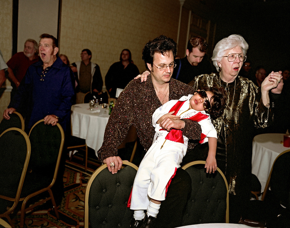 Sleeping Elvis, Kissimmee, Florida, 2005..During the closing ceremonies at the Elvis Presley fan club's dinner one erstwhile Elvis look-a-like can no longer stay awake.  On the right is Elvis Presley's last nurse, Marian Cocke...Photo by Susana Raab.