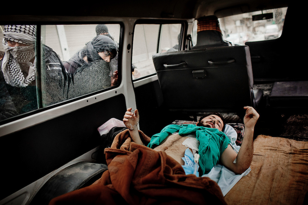 A wounded fighter from the Free Syrian Army taken from an hospital into Sabka, a town under control of the Free Syrian Army, is watched by other fighters in a checkpoint, Sabka, outskirts of Damascus, January 27, 2012. Photo/Tomas Munita