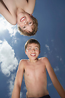 Portrait of two boys (6-11) bending down view from below