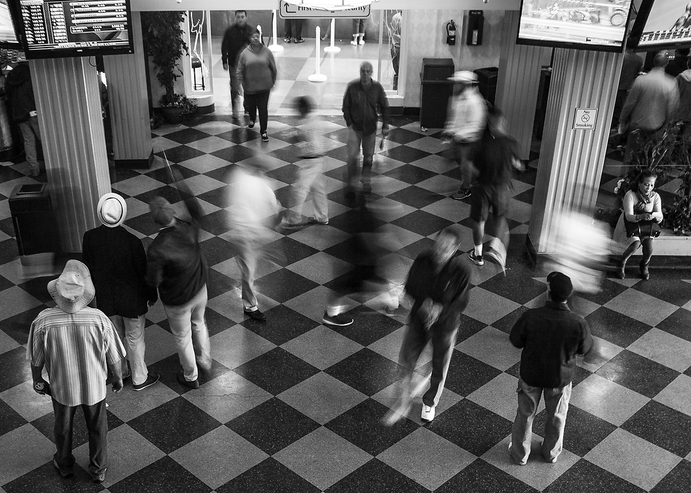 A group of people gather in front of flat screen TVs as others make their way through the hallway at a horse racing event at Santa Anita Park, in Arcadia, CA. on the day of the Kentucky Derby, celebrated May 6, 2017.<br /> <br /> Photo by Samuel Navarro