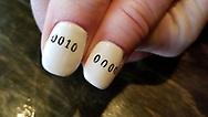 Close up of a woman's fingernails bearing binary code, Windsor, Canada.