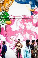 Men hang out near a painted mural at the Little India MRT station in Singapore.