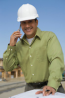 Architect talking on mobile phone over blueprints