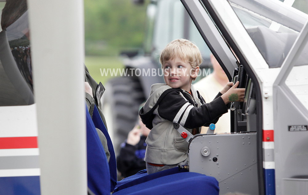 Montgomery, New York - A young boy sits in the cockpit of an airplace during the Touch-A-Truck event to benefit the United Ways of Orange and Dutchess counties at Orange County Airport on May 14, 2011.