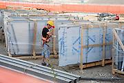 A worker with a helmet, gloves and safety belt, looking at the right aluminum panel at the building site of Expo 2015, Rho, June 2014. &copy; Carlo Cerchioli<br /> <br /> Un operaio, con caschetto, guanti e cintura di sicurezza, alla ricerca del pannello di alluminio da montare nel cantiere di Expo 2015, Rho, giugno 2014.