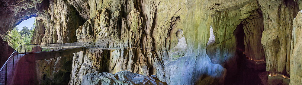 "In Slovenia, the wonderful self-guided Part 2 of Skocjan Caves walking tour follows the mysterious Reka River from Mala Dolina (Small Doline, a sinkhole) through Mahorcic Cave (Mahorciceva jama) upstream underground for 350 meters over exciting bridges and dimly lit passages. From a large-scale karst drainage, the Reka River has carved and dissolved dramatic subterranean passages through limestone over several million years. Karst topography is a geologic formation of dissolving bedrock. Our word for ""karst"" likely evolved from the Slovene noun kras and earlier proper noun Grast, referring to Slovenia's Karst Plateau. Visit Skocjan Caves (Skocjanske jame) Regional Park near Divaca, in the Littoral region of the Republic of Slovenia, Europe. UNESCO has honored Skocjan Caves as a World Heritage Site. This panorama was stitched from 14 overlapping photos."