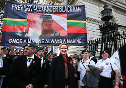 © Licensed to London News Pictures. 28/10/2015. London, UK. Claire Blackman (C) stands with veteran Royal Marines outside Downing Street during a rally calling for her husband, Sgt Alexander Blackman to be released.  Sgt Blackman was sentence for killing a Talliban insurgent in Afghanistan in 2011. He was convicted of murder at a court martial in 2013.   Photo credit: Peter Macdiarmid/LNP