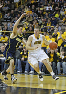 February 19 2011: Iowa Hawkeyes guard Matt Gatens (5) drives around Michigan Wolverines guard Stu Douglass (1) during the first half of an NCAA college basketball game at Carver-Hawkeye Arena in Iowa City, Iowa on February 19, 2011. Michigan defeated Iowa 75-72 in overtime.