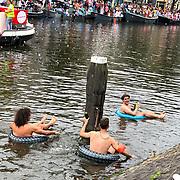 NLD/Amsterdam/20190803 - Gaypride 2019, jongesn in opblaasband in het water van de gracht