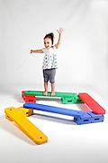 Indoor playground young girl of 4 balances On white Background MR available