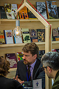 Discussions, negotiations and deals go on at tables all over the fair. London Book Fair, Olympia, London, UK, 14 Apr 2015.