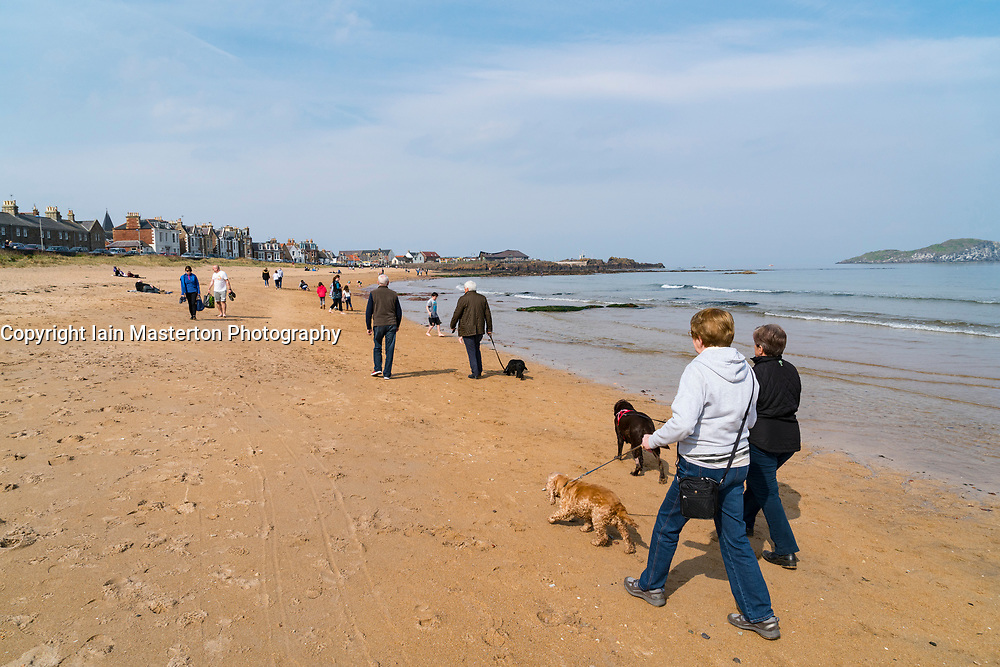 People walking on beach at North Berwick on Forth estuary in East Lothian, Scotland, United Kingdom.