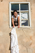Munzur Valley, Turkey - July 12, 2014 - A woman shakes out a tablecloth from the second-story window of a house in the Munzur Valley.   CREDIT: Michael Benanav for The New York Times