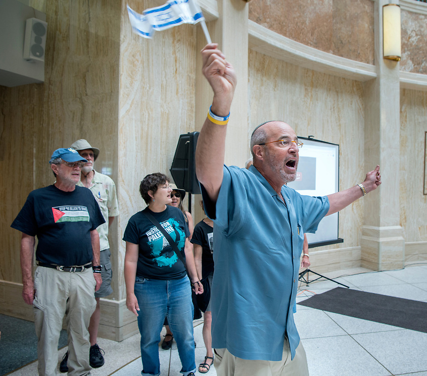 em060717e/a/Richard Lieberman, right, from Santa Fe, sings a Jewish song to drowned out Susan Schuurman, center, with Albuquerque Center for Peace and Justice, and a group of protesters that interrupted a ceremony commemorating the 50th anniversary of the reunification of Jerusalem held in the Rotunda of the State Capitol in Santa Fe Wednesday June 7, 2017. The events was held to watch live streaming of commemoration events in Jerusalem and Washington D.C. Around 40 people including some state legislators attended the event at the State Capitol. Around 20 people protested the event outside the Roundhouse, for the most part. (Eddie Moore/Albuquerque Journal)