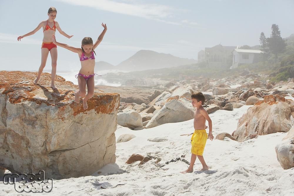 Three Children Playing on Rocky Beach