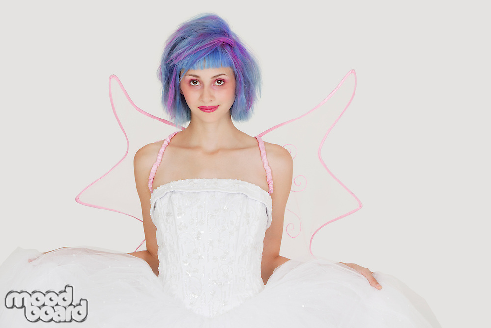 Portrait of beautiful young woman dressed as angel with dyed hair against gray background