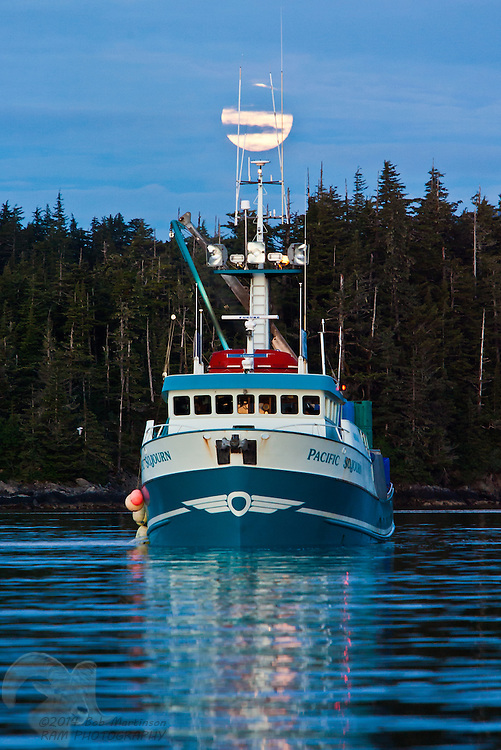 The fishing vessel Pacific Sojourn sits by Crafton Island in Prince William Sound, Alaska as the Solstice moon rises above.
