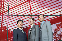 Businesspeople Standing outside beside red Building low angle view