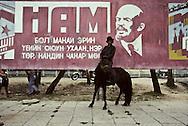 Mongolia. man on horse in front of a big portrait of Lenin / Pancarte vieillie de propagande communiste.<br />  - Le Parti, c'est l'essence même de l'honnêteté, de l'honneur et de l'intelligence de notre époque! - <br /> Un cavalier de passage pose devant une pancarte tombée en désuétude dans une société en pleine transfomation des mentalités. (Ville de ULIASTAI, capitale de l'aymag de ZAVQAN; le 20 juillet 1992).