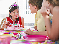 Girl (7-9) with birthday cake talking to guests at birthday party