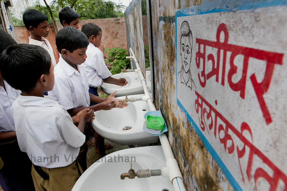 Village Bhatari, Pombhurana Block, Dist. Chandrapur. .Children wash their hands after using the toilet facility,  at Zilla Parishad Higher Primary School in Bhatari. Woodland and Govenrment schools have provided facilities for children with seperate toilet for boys and girls, handwashing platform, use of soap before mid-day meal and after using toilet, clean toilet with water facility, clean mid-day meal kistchen and safe drinking water as a part of Bio Village project.  Bio Village is a part of the over all obejective of the Water Hygiene and Sanitation project ( WASH). UNICEF partners with the State nodal Department, Water Supply and Sanitation Department under the State Government and District level TSC, Divisions, Key resource Centres and NGOs. Special initiatives have been undertaken in the State such as Bio-Village Project in IDPs, WASH Compliance in Schools, Multiple Use Water Services project (MWUS), Sanitary Napkin production and promotion of menstrual hygiene, Risk based rapid assessment of water quality as per JMP manual and NGP concurrent monitoring.UNICEF India/2012/Vishwanathan